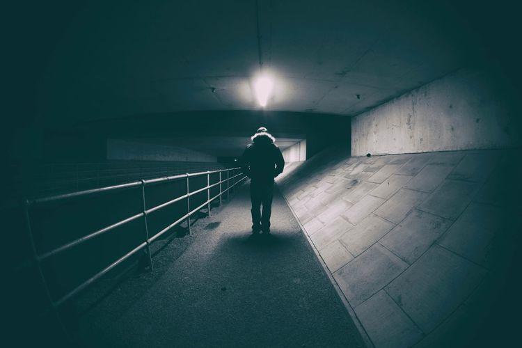 Rear view of man walking in illuminated corridor