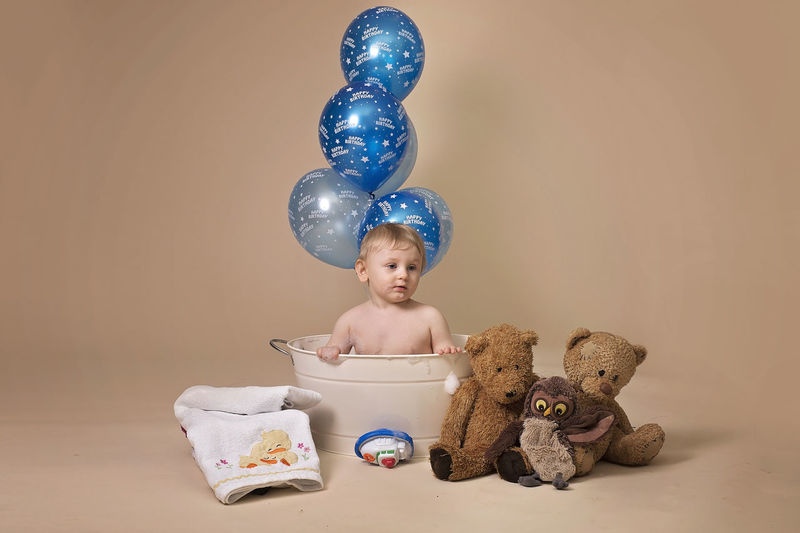 Shirtless Boy In Baby Bathtub By Stuffed Toys And Helium Balloons Against Beige Background
