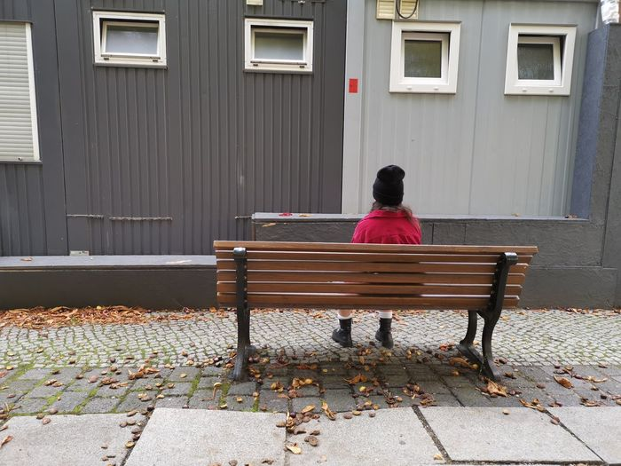 Rear view of woman sitting on bench against building
