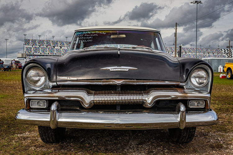 Close-up of vintage car against cloudy sky