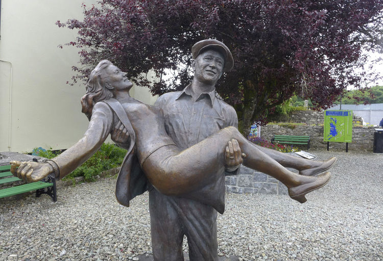 Statue John Wayne Carring Maureen O'Hara,Cong Film, John Wayne Statue Art And Craft Cong, Craft Creativity Day Female Likeness Flower Human Representation John, Male Likeness Maureen Maureen O'Hara Nature No People Park Park - Man Made Space Plant Quiet Man Representation Sculpture Smiling Statue Tree