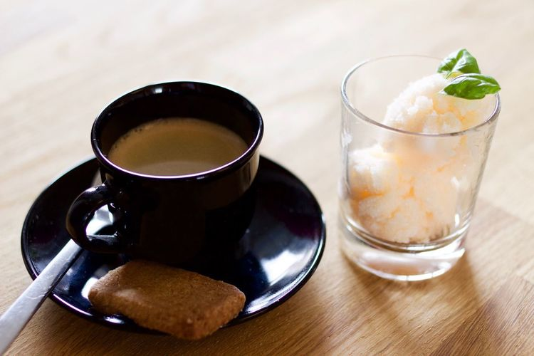 Coffee cup with cookie and sorbet in glass garnished with mint leaves