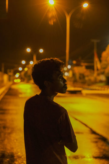 Side view of young man looking at illuminated city street