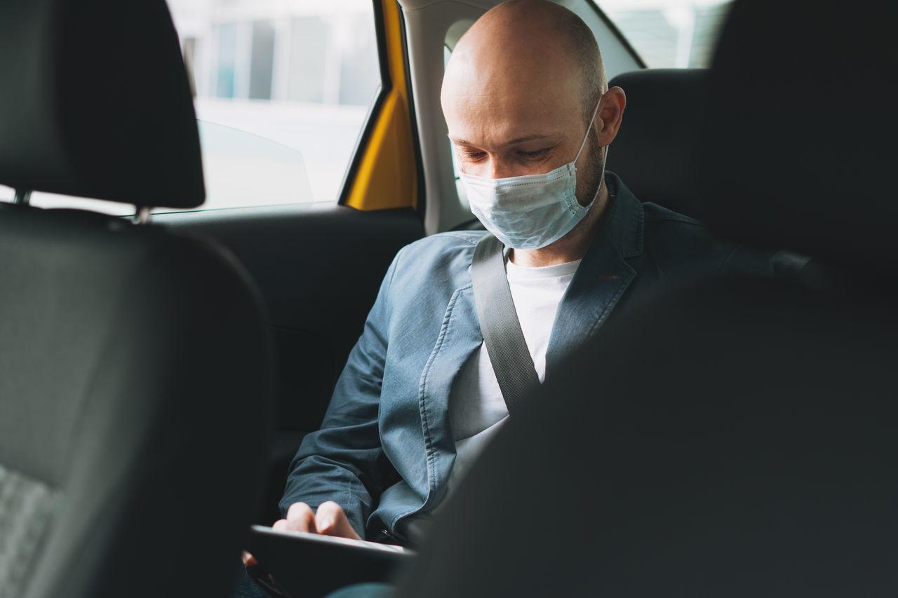 Man wearing mask using digital tablet in car