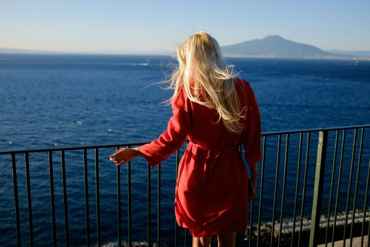Rear view of woman standing by railing while looking at sea