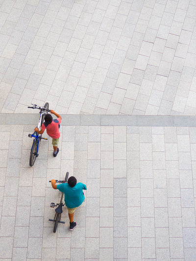 High angle view of friends with bicycle on cobbled street
