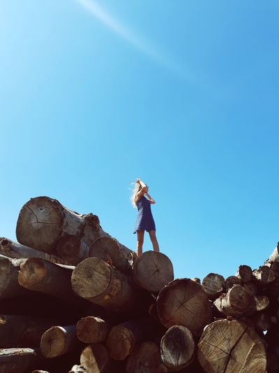 Low angle view of woman standing on logs against clear blue sky