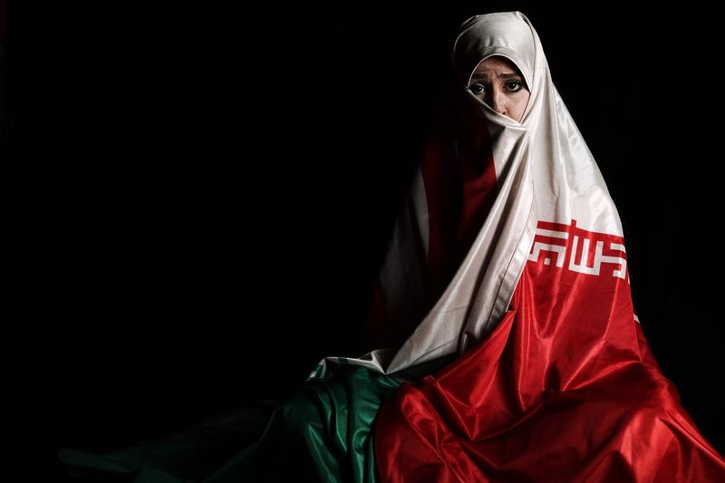 Portrait of woman wrapped in iranian flag against black background