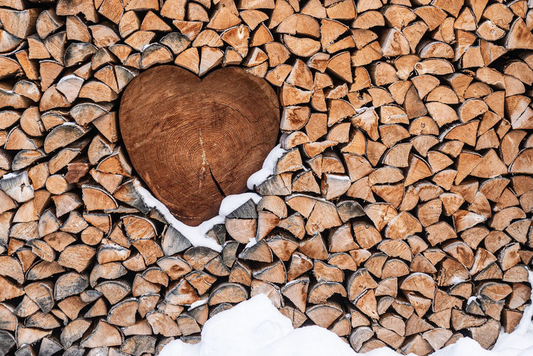 Wood for the fireplace arranged in an artistic way with a wooden heart. natural wood background.