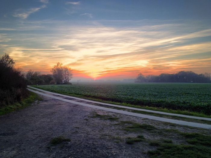 Road by landscape against sky during sunset