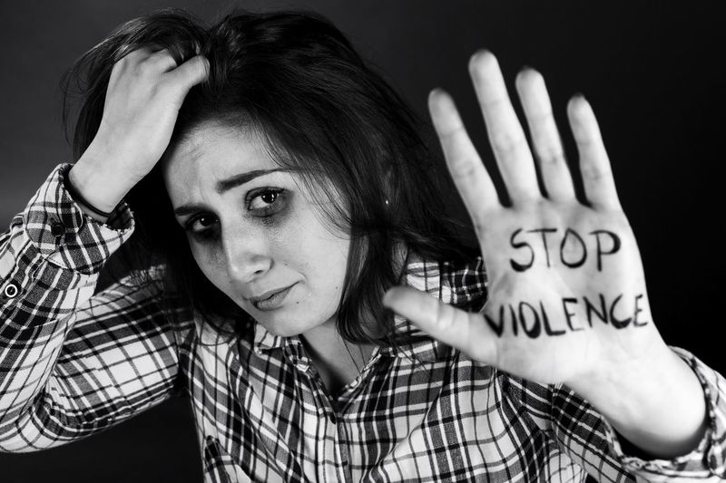 Portrait of woman with hand in hair showing stop violence text on palm