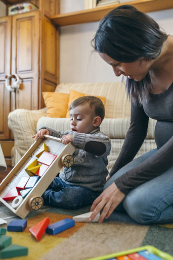 Mother looking at cute son playing with toys at home