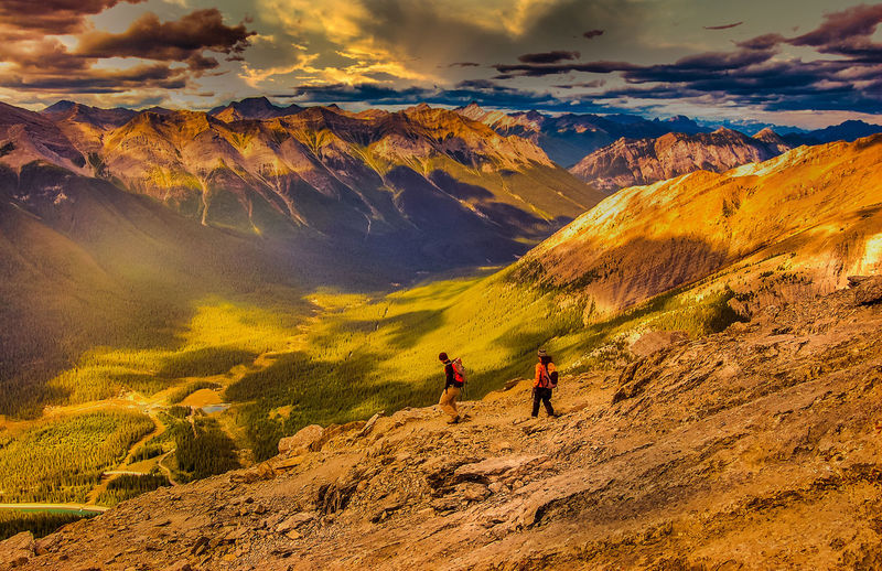 People on mountain against sky during sunset