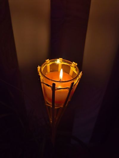 High angle view of lit candle in darkroom