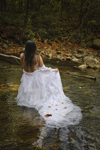Rear view of woman in front of stream in forest