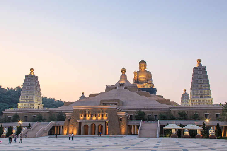 Kaohsiung, Taiwan - December 15, 2014: Sunset at Fo Guang Shan buddist temple of Kaohsiung, Taiwan with many tourists walking by. Architecture Art ASIA Asian  Asian Culture Buddha Buddha Statue Built Structure Clear Sky Famous Place Fo Guang Shan History Kaohsiung Leisure Activity Lifestyles Low Angle View Religion Sky Summer Taiwan Temple - Building Tourism Tourist Tradition Travel Destinations
