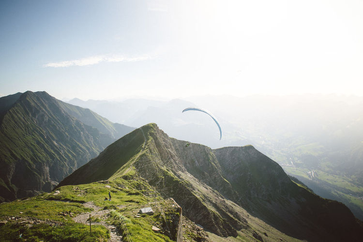 Scenic view of mountains with person paragliding against sky