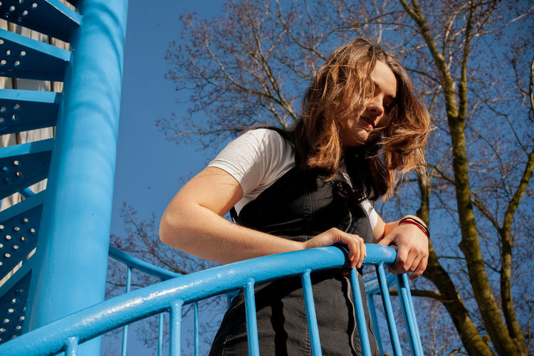 Low angle view of woman looking away while standing on railing