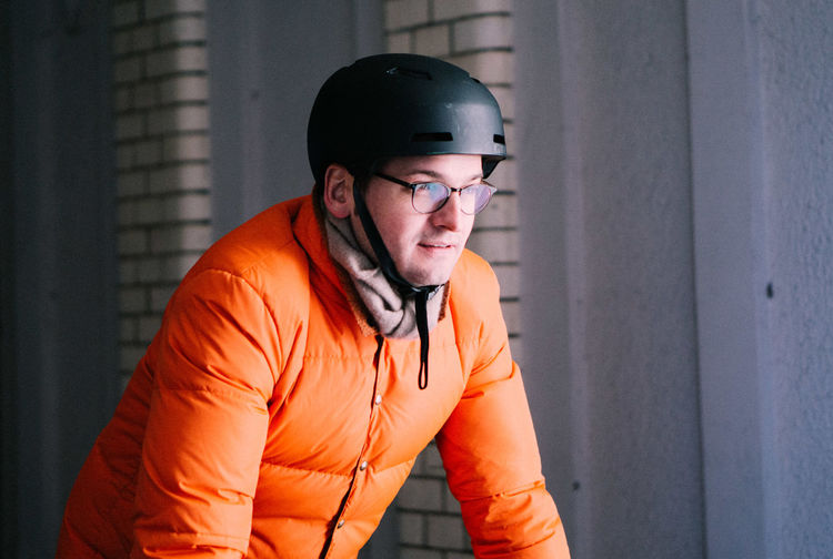Mature man in warm clothing wearing cycling helmet while looking away