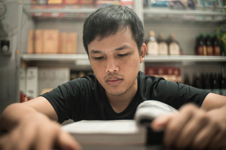 Concentrated man reading book at table