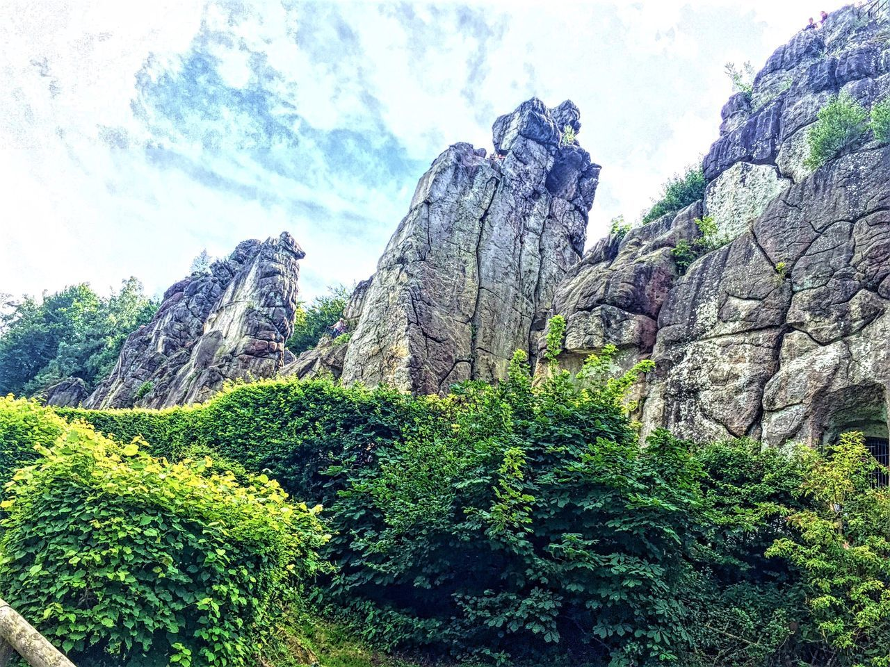 nature, beauty in nature, mountain, rock formation, day, green color, rock - object, tree, tranquility, scenics, outdoors, tranquil scene, no people, sky, physical geography, low angle view, plant, landscape, growth, grass