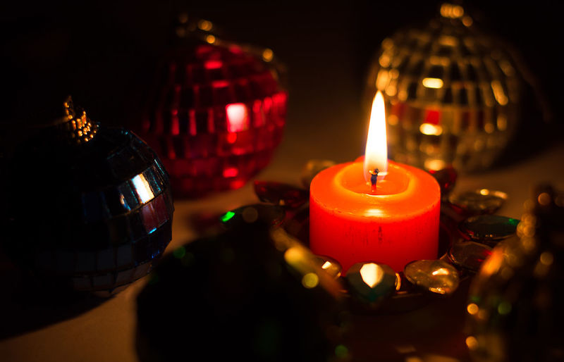 Close-Up Of Lit Candle Amidst Christmas Ornaments On Table