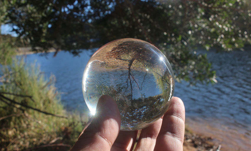 Tranquility Glass Nature Focus On Foreground Glass Ball Reflections People Day Sky Outdoors Planet Earth Fragility Refraction Eyesight Holding Close-up Fortune Telling Human Body Part Bubble Reflection Crystal Ball Ball Tree Water Beauty In Nature
