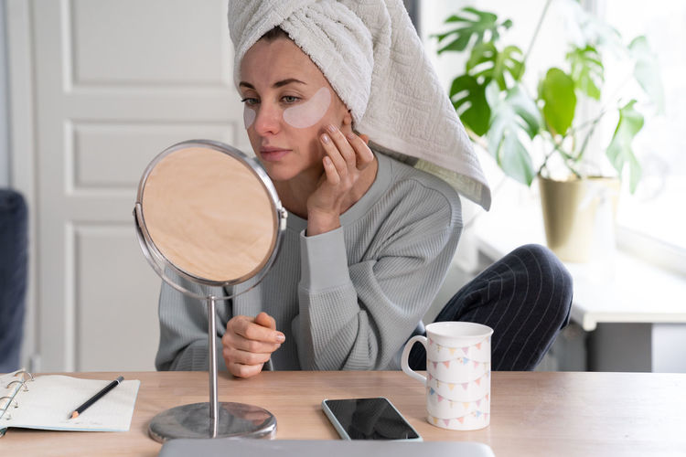 Woman applying eye patches while sitting at home