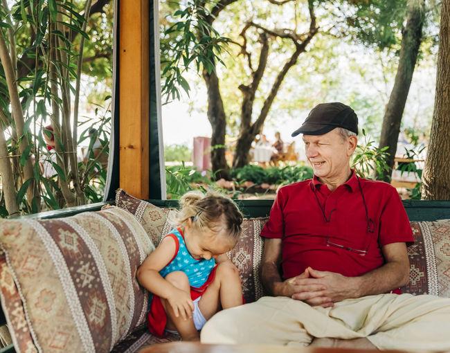 senior man sitting with granddaughter in garden