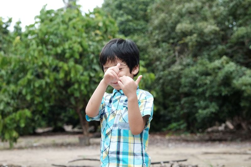 Boy gesturing while playing in park