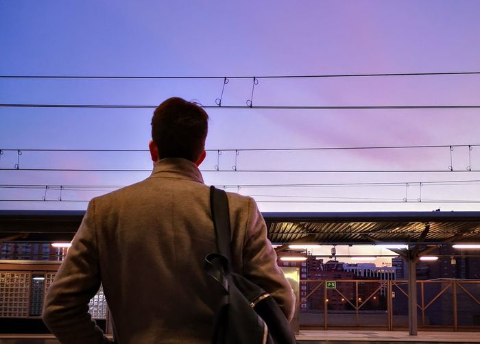 Waiting at the train station Madrid Man Sky Colours Colors Sunset Coat Model Train Train Station Waiting Wait Backpack Back Looking At View EyeEm Gallery Eyemphotography City City Street Calm Thoughtful Streetphotography Rear View Standing Electricity Pylon Working Men Sky Power Line  Cable