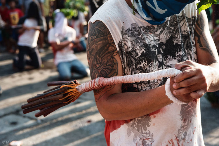 Midsection of man holding rope while standing outdoors during traditional festival