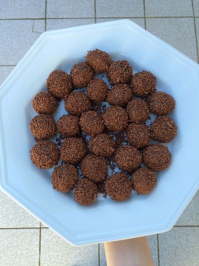 Cropped Image Of Hand Holding Brigadeiros In Plate