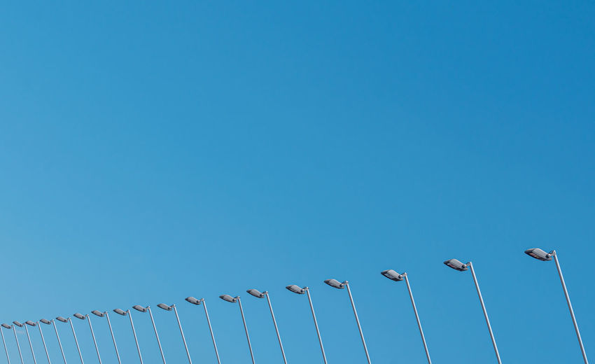 Low angle view of birds perching on cable against blue sky