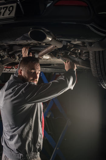 Portrait of male mechanic repairing car at auto repair shop