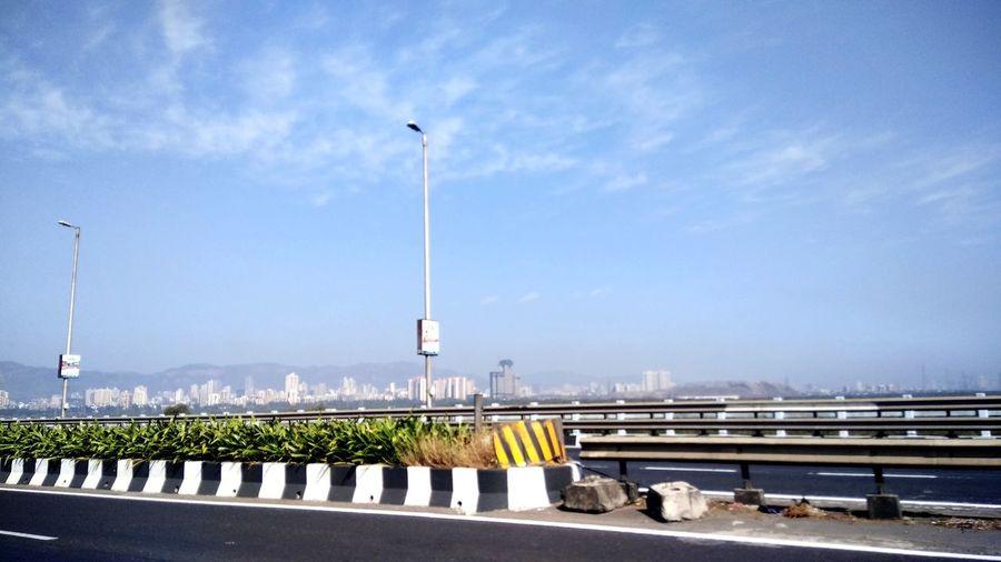 View of bridge over street against blue sky