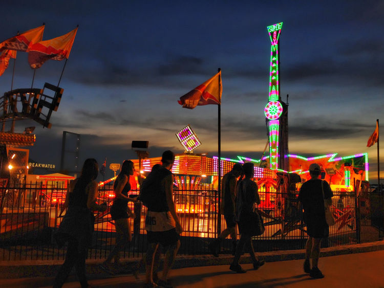 People going to the fair after sunset. Fair Fairground Funfair Funfair Streetphotography Illuminated Leisure Activity Night Outdoors People Walking  Real People Sunset Sunset Silhouettes