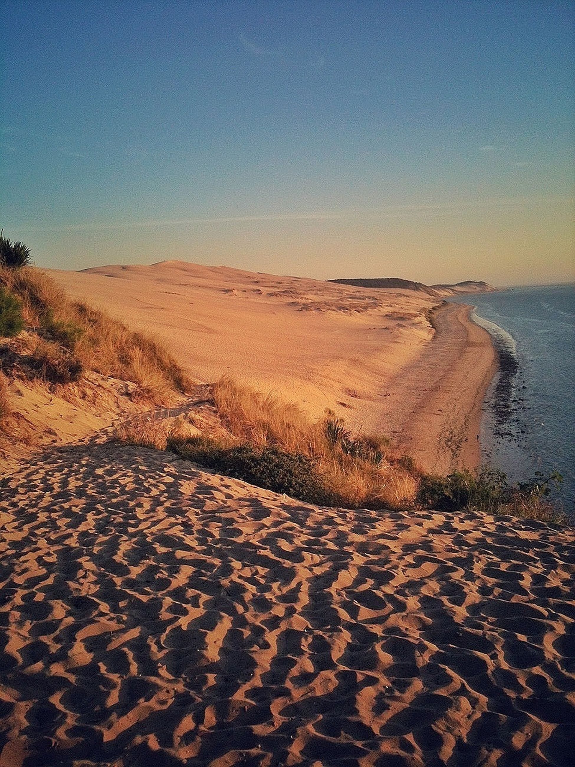 sand, beach, sea, tranquility, tranquil scene, shore, water, clear sky, scenics, beauty in nature, nature, horizon over water, copy space, coastline, idyllic, sky, remote, desert, non-urban scene, footprint