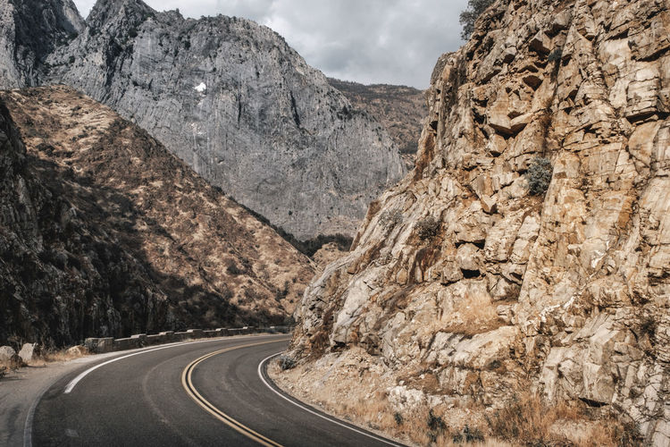 Road passing through rock formation against sky
