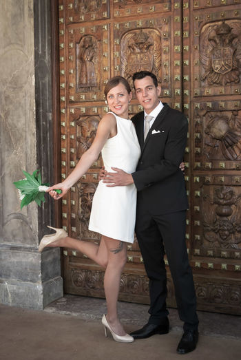 Portrait of bride hugging bridegroom against ornate door