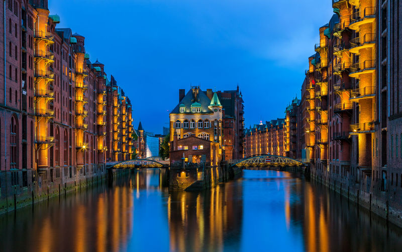 Canal amidst buildings in city at dusk
