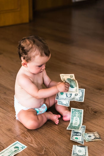 High angle view of boy playing with currency on floor