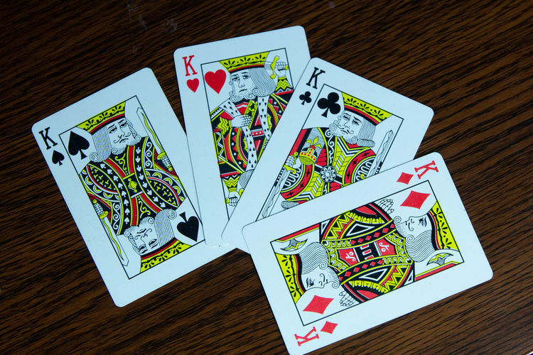 Arts Culture And Entertainment Cards Communication Female Likeness Gambling Group Of Objects High Angle View Human Representation Indoors  Leisure Activity Leisure Games Luck Multi Colored No People Representation Still Life Table Text Western Script Wood - Material