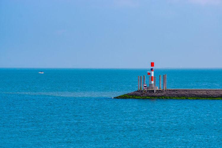 Lighthouse on sea against clear blue sky
