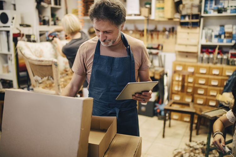 Male craftsperson holding digital tablet while opening cardboard box in workshop