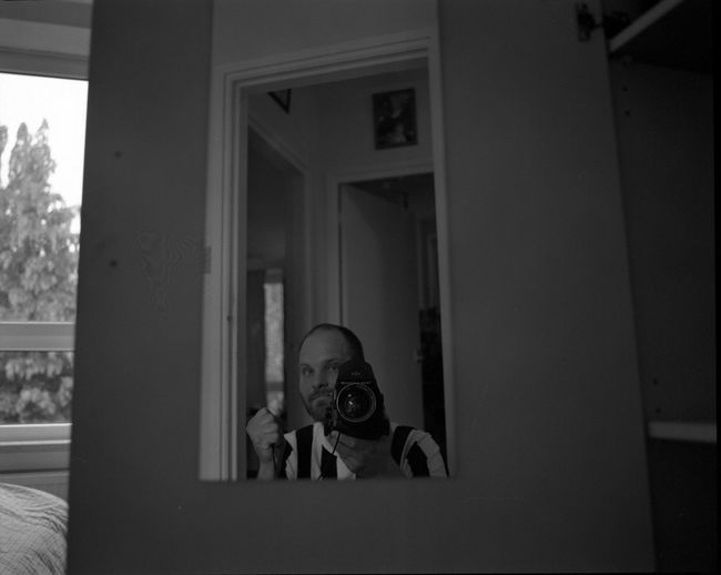 Reflection Of Man Photographing In Mirror At Home