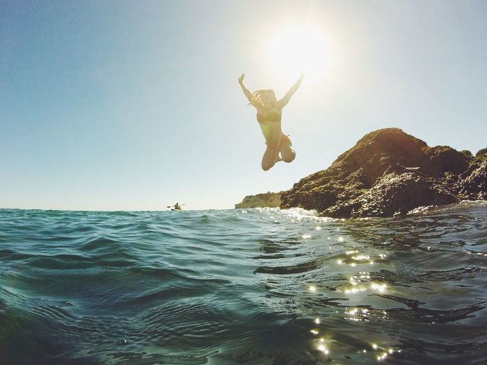 Excited Woman Jumping In Sea At Praia Dos Beijinhos Against Sky On Sunny Day