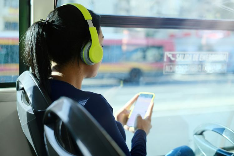 Rear view of man using mobile phone in bus