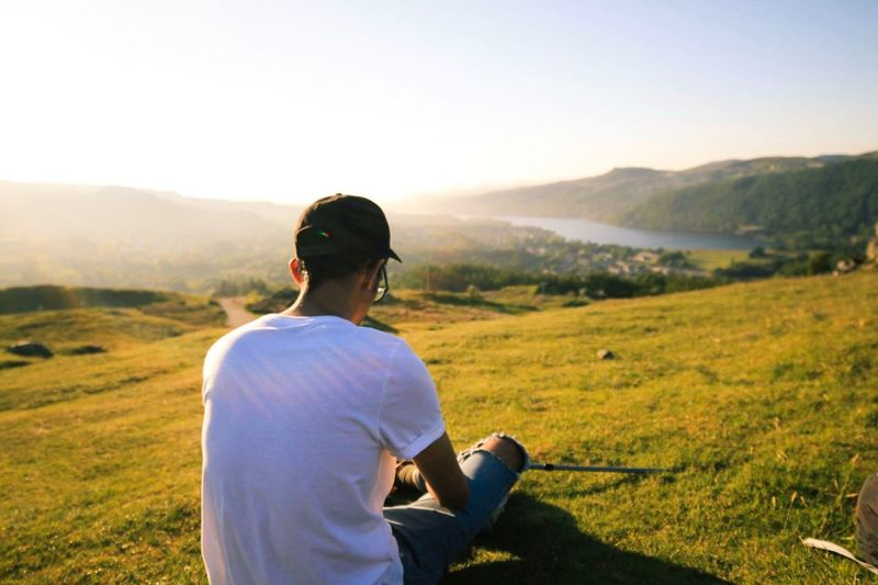 Rear view of man relaxing on grassy field during sunny day