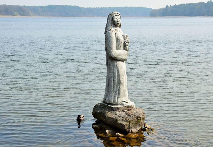 Am Ufer des Sees begrüßt uns eine lebensgrosse Frau aus Granit. Mit dem Bildnis einer Nonne hat es folgende Bewandtnis: Das Mädchen Amelie aus einer adligen Familie liebte den armen Bauernsohn Jacob. Um dem ein Ende zu machen, steckten die hartherzigen Eltern ihre Tochter in das nahe Kloster. Jacob entführte jedoch seine Geliebte. Beide blieben verschwunden. Wir wissen nicht ob sie im See ertrunken sind, oder andernorts ihr Glück gefunden haben..... Water Lake Sculpture Human Representation Art And Craft Representation Statue Day Nature No People Bird Male Likeness Waterfront Creativity Lake View Lakeside